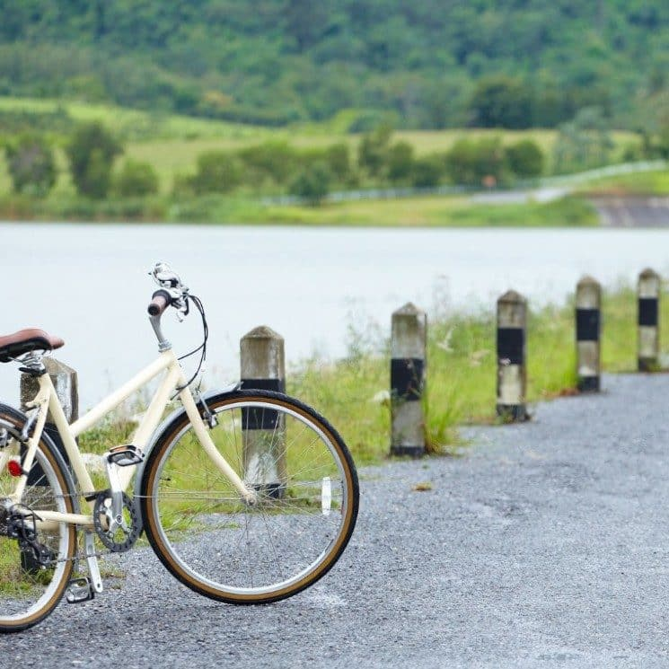 Path near a body of water with a white bicycle leaning against a post