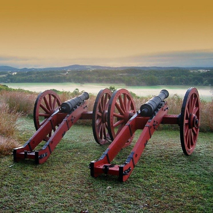 Two historical wagon-wheel style cannons on a ridge facing a body of water