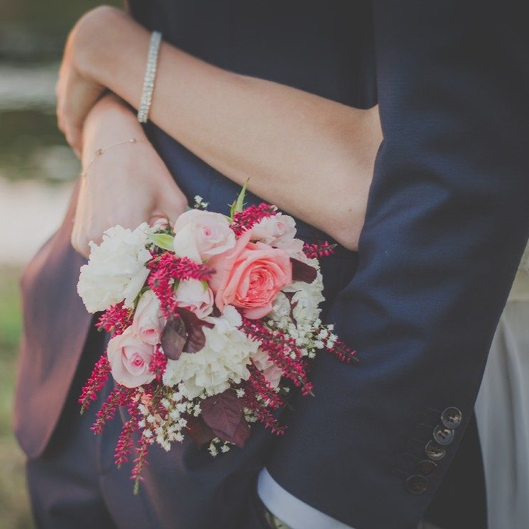 Woman with a diamond bracelet and bouquet of flowers hugging a man in a dark suit