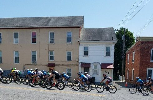 A group if cyclists in a row going up a hill in front of buildings