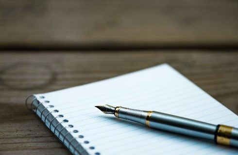 A white spiraled notebook and fountain pen on a wooden table