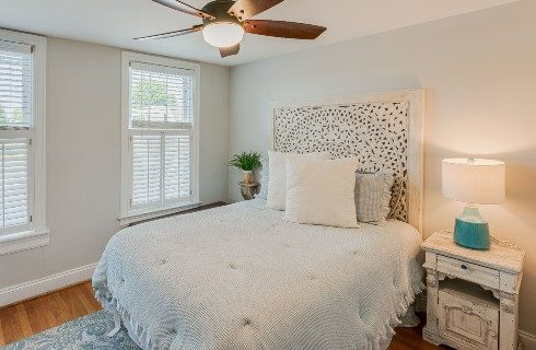 Elegant bedroom with queen bed and decorative headboard, dresser with lamp and two windows