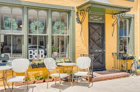 Front facade of a yellow brick building with large windows, black door and outdoor patio tables and chairs
